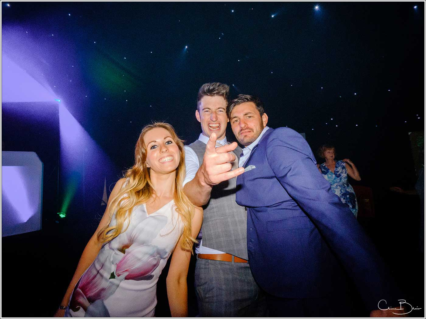 Coombe Abbey wedding photography showing 3 guests playing up to the camera on the dance floor