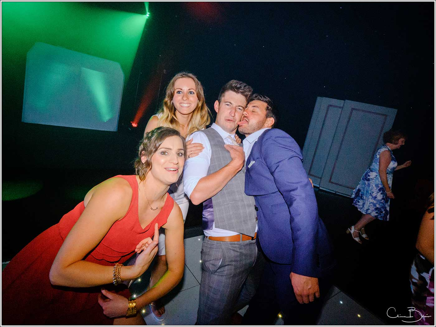 Coombe Abbey wedding photography showing 4 guests playing up to the camera on the dance floor