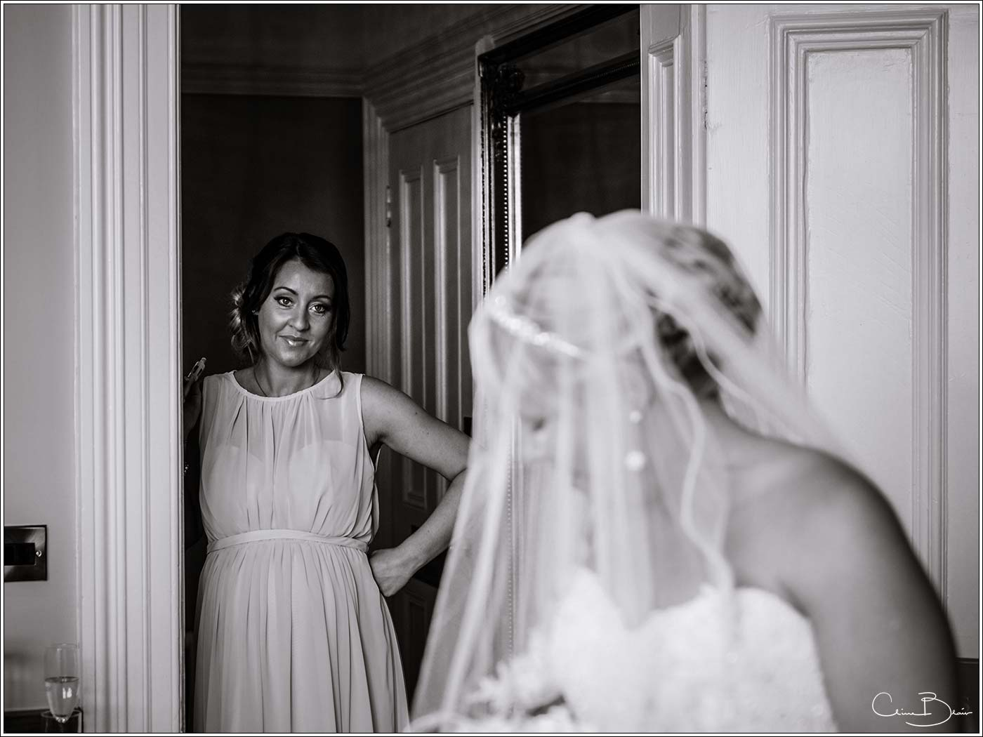 Bridesmaid looking at Bride during the morning preparations as photographed by a recommended Pendrell Hall photographer