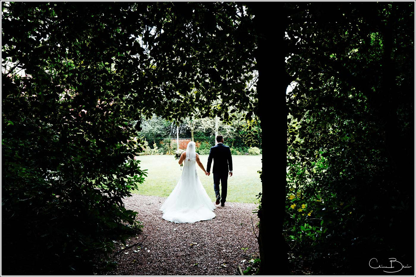 Bride and groom walking alone in the secret garden by Pendrell Hall wedding photographer Clive Blair