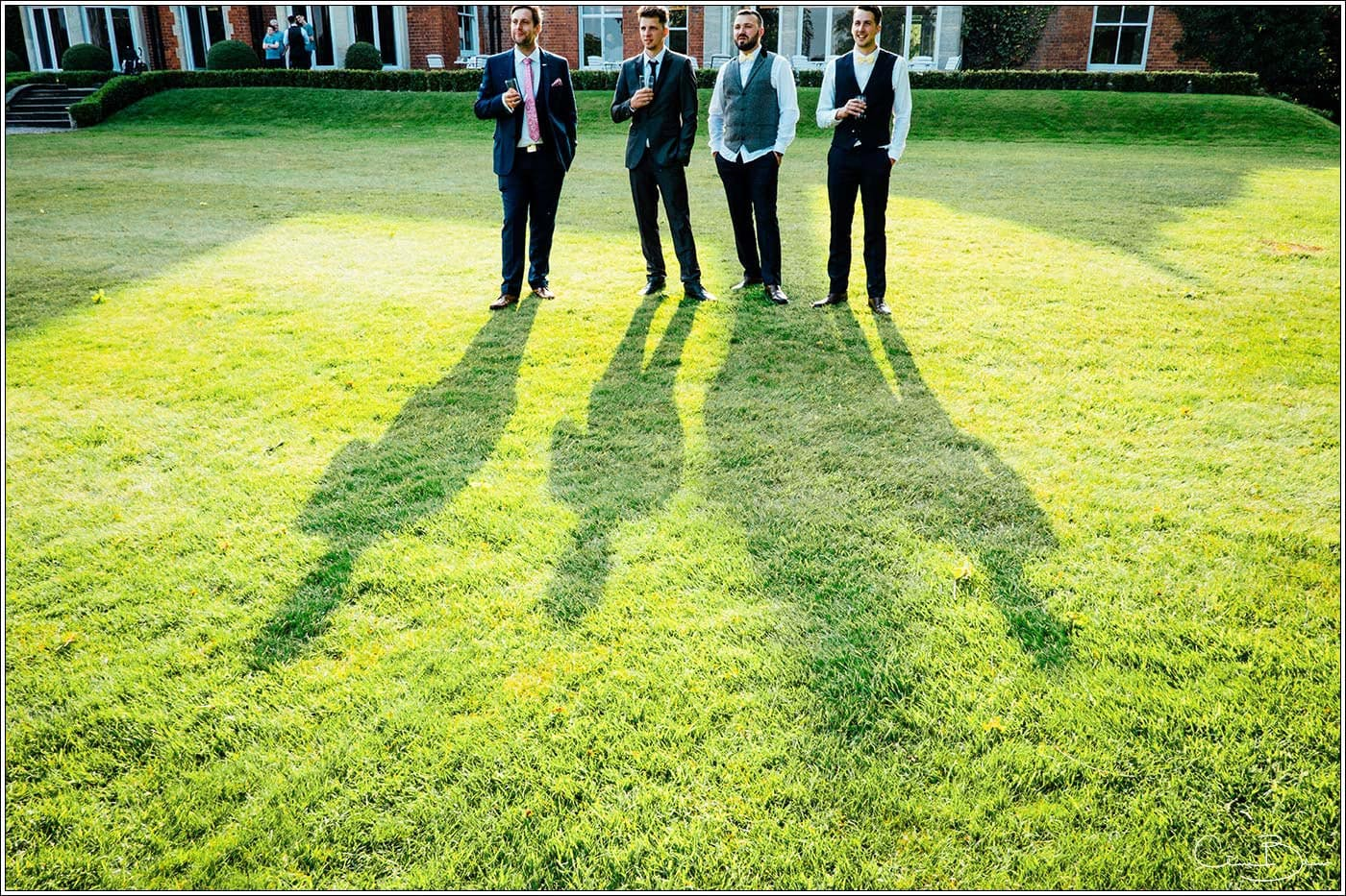 Long shadows of men standing in the sun by Pendrell Hall wedding photographer Clive Blair