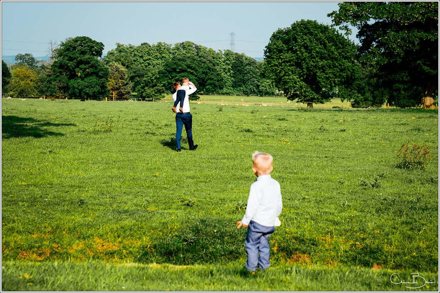 Child watching guest taking another child into a field of cows at Pendrell Hall as photographed by a recommended Pendrell Hall photographer
