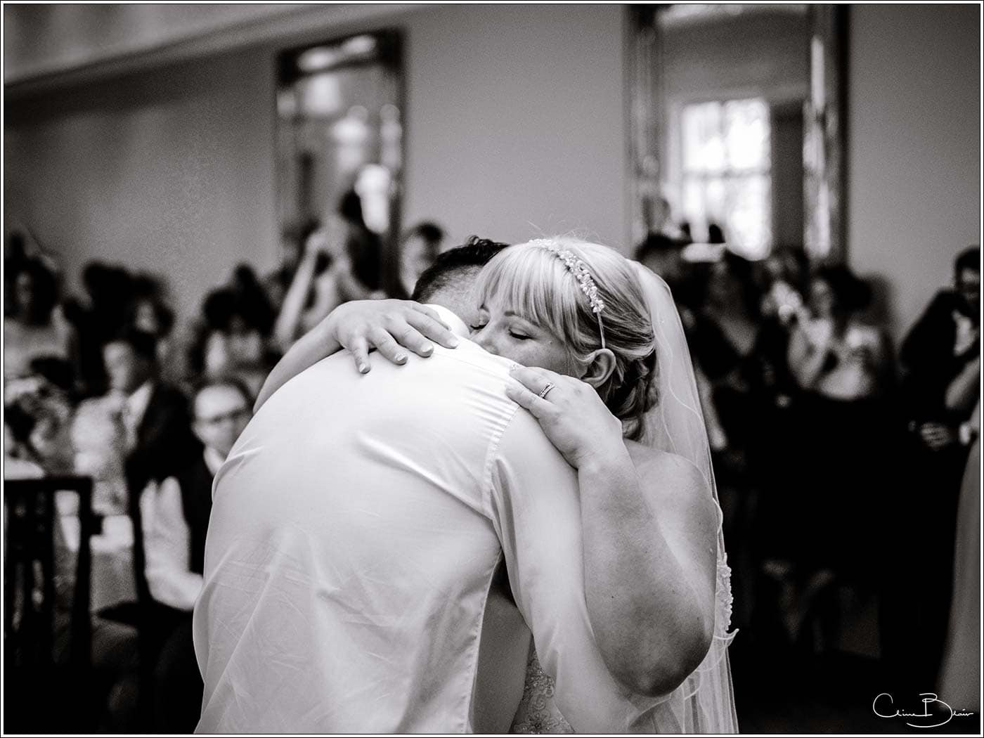Bride holding groom during their first dance by Pendrell Hall wedding photographer Clive Blair