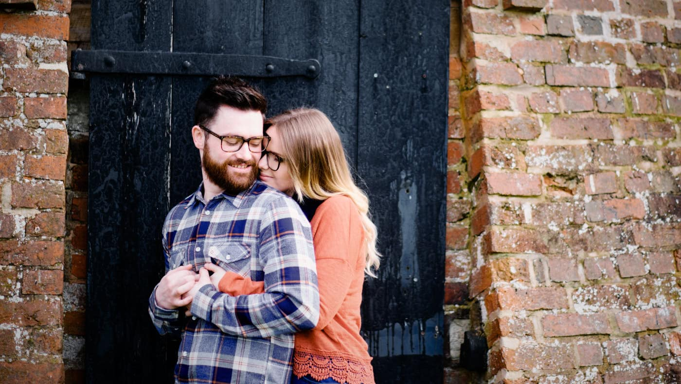 Engaged couple by rustic building at Avoncroft Museum as photographed by Avoncroft Museum pre-wedding shoot photographer Clive Blair
