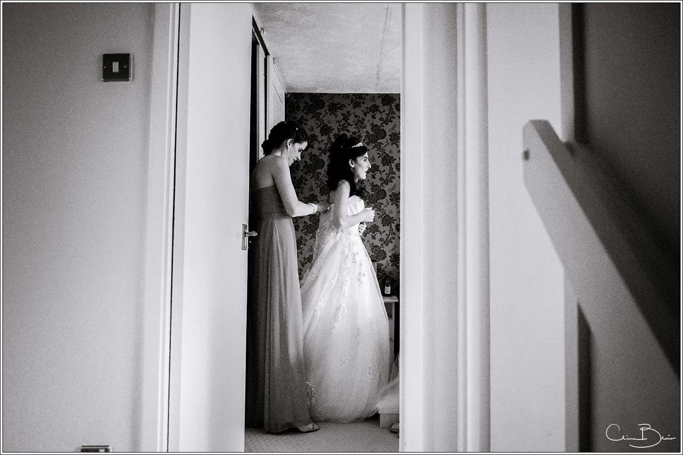Bride putting on wedding dress: Bank House Wedding Photographer Clive Blair Photography. Documentary Birmingham Wedding Photographer