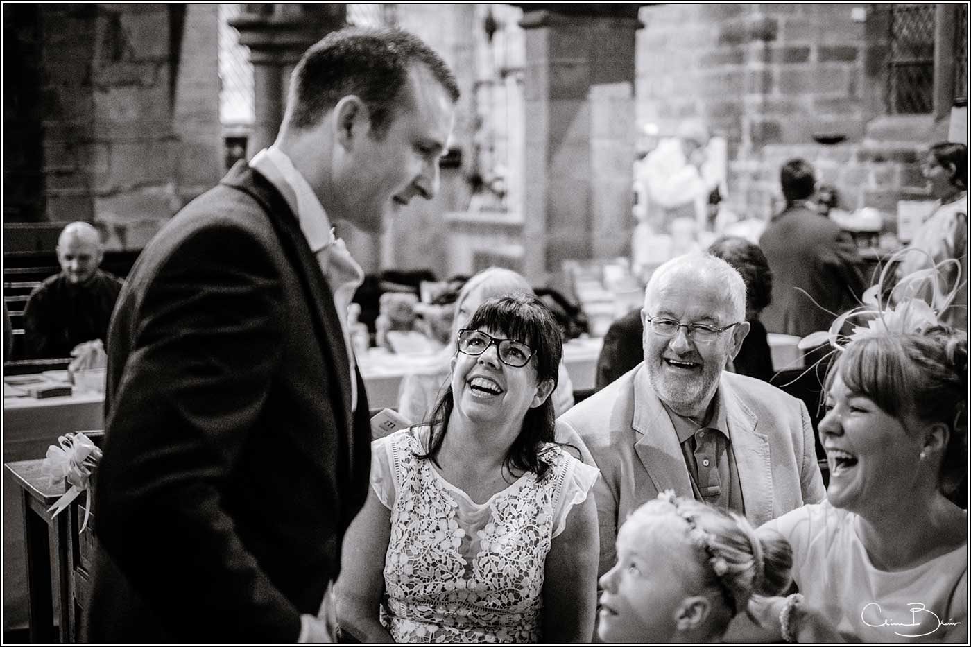 Groom in church with guests: Bank House Wedding Photographer Clive Blair Photography. Documentary Birmingham Wedding Photographer