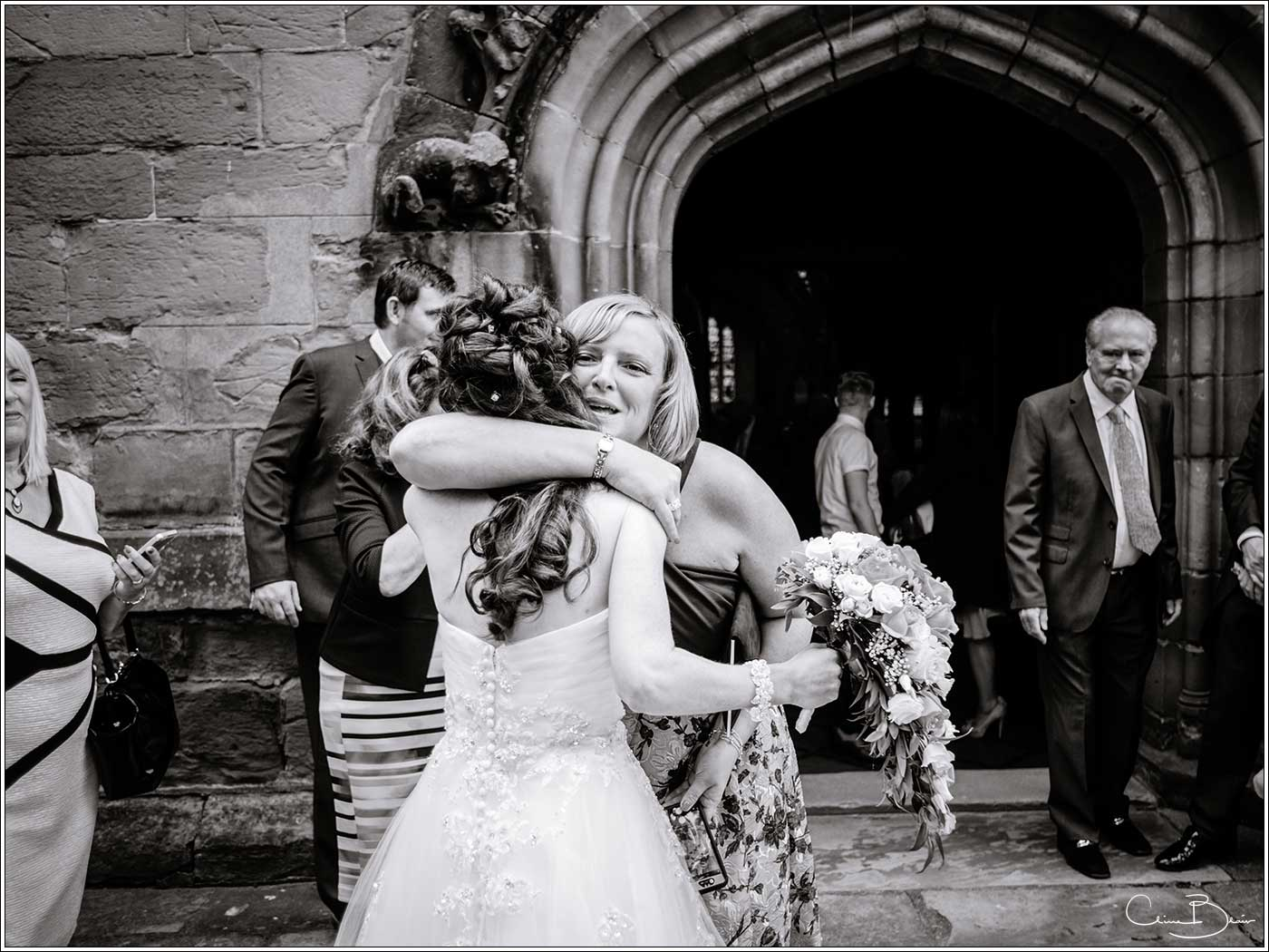 Bride being hugged by guest: Bank House Wedding Photographer Clive Blair Photography. Documentary Birmingham Wedding Photographer