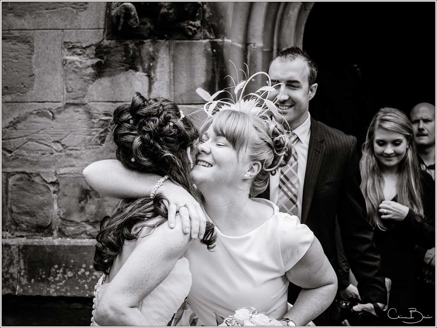 Bride being hugged by woman: Bank House Wedding Photographer Clive Blair Photography. Documentary Birmingham Wedding Photographer