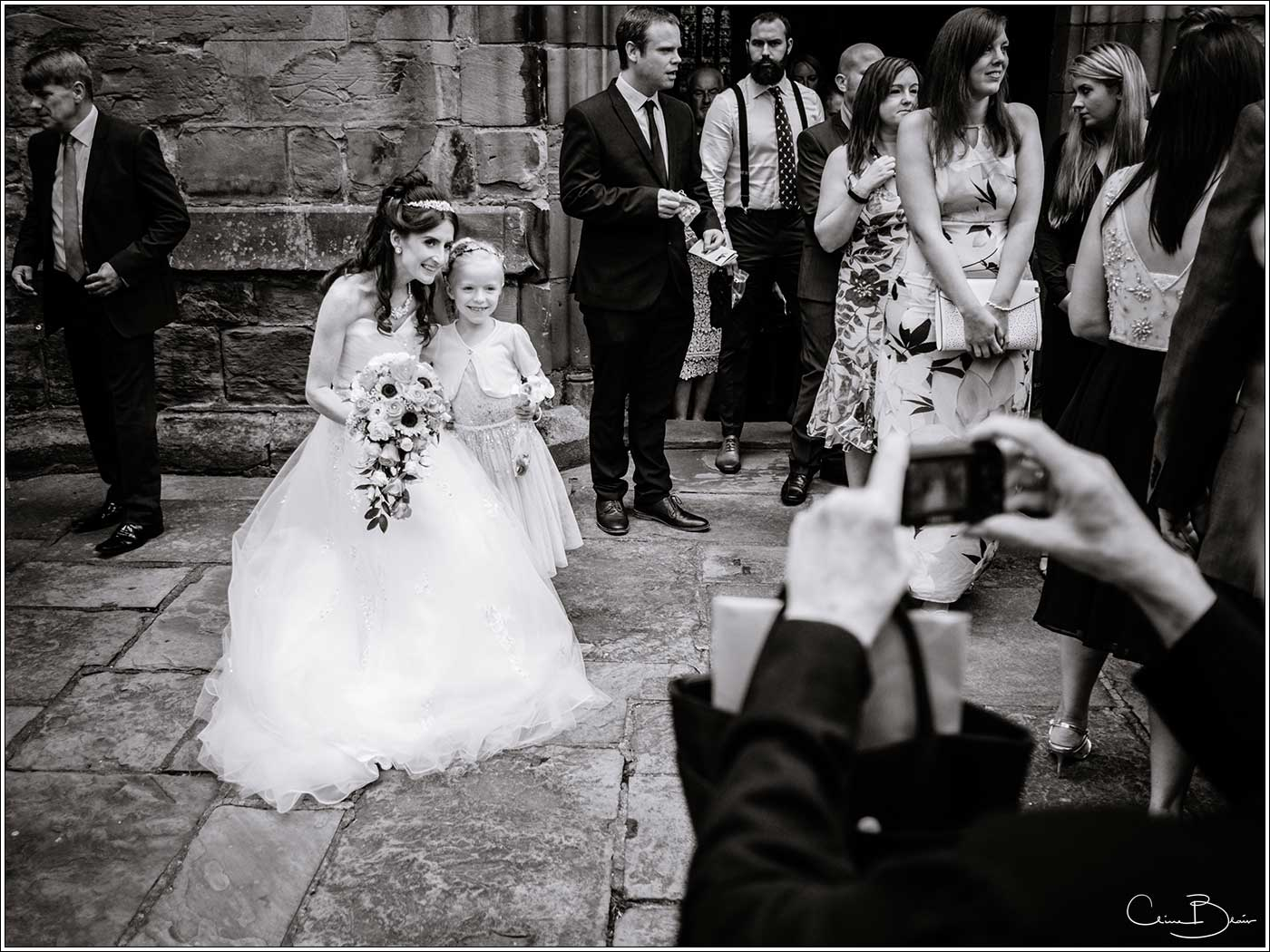 Bride having photo taken with little girl: Bank House Wedding Photographer Clive Blair Photography. Documentary Birmingham Wedding Photographer