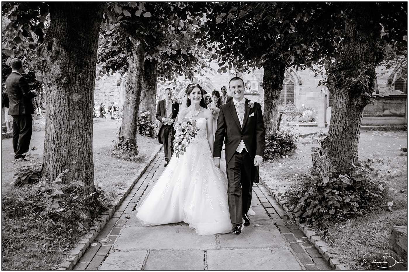 Bride and groom exciting church ground: Bank House Wedding Photographer Clive Blair Photography. Documentary Birmingham Wedding Photographer