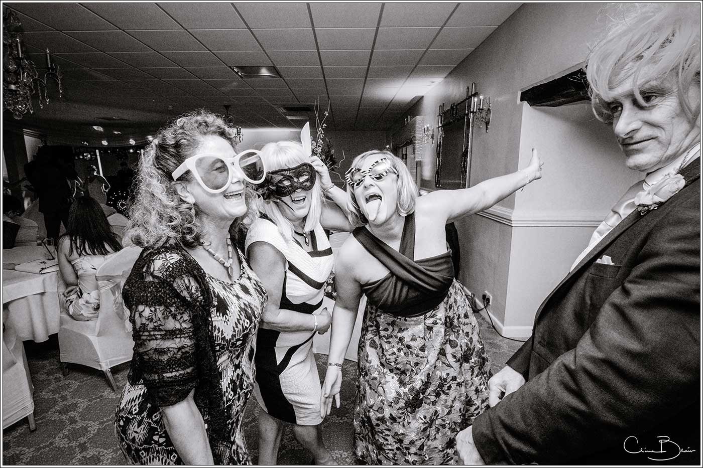 Wedding guests dressed in photobooth glasses and wigs at Bank House