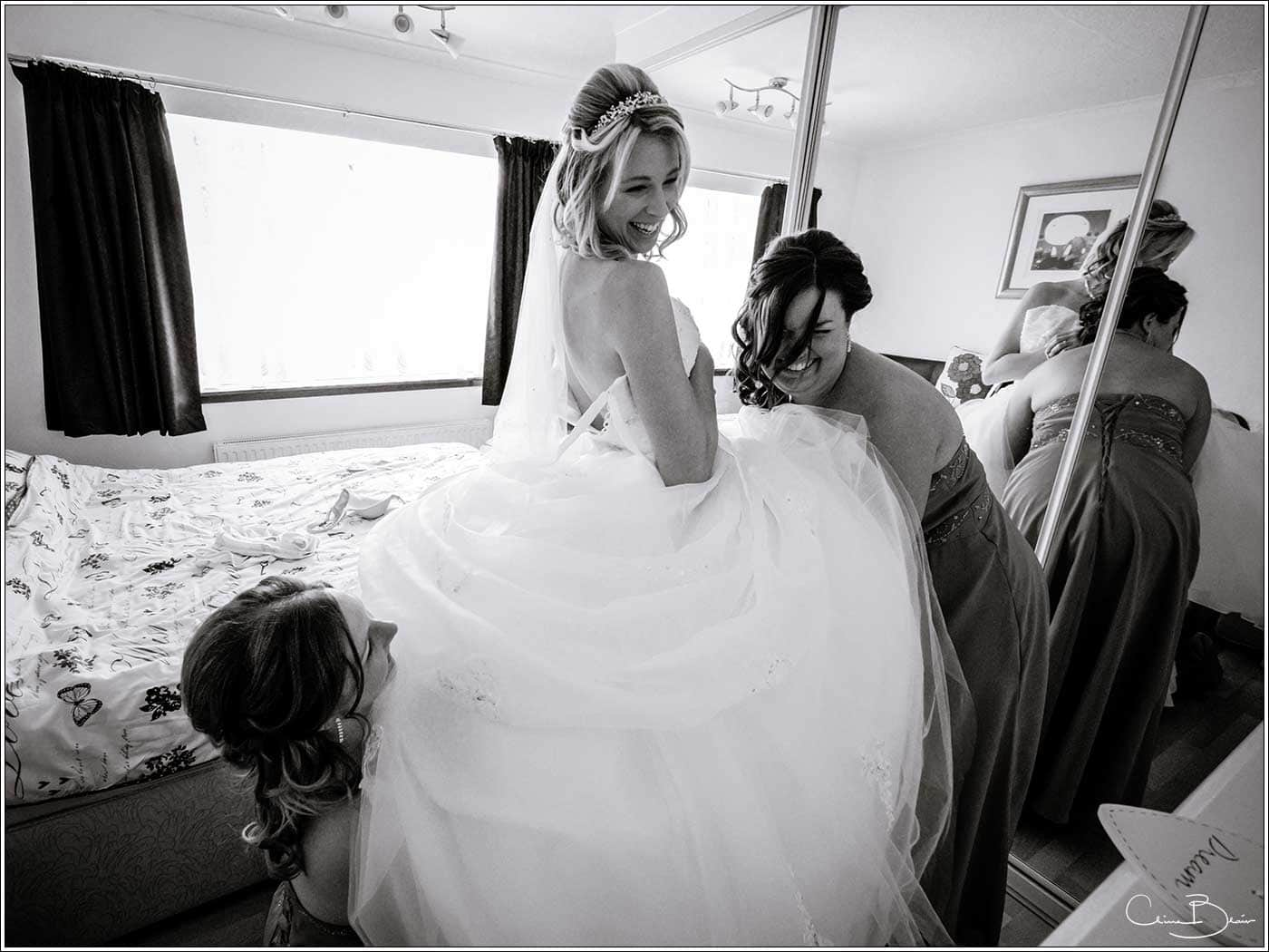 Bride being helped into dress by maids-by Hampton manor wedding photographer Clive Blair Photography