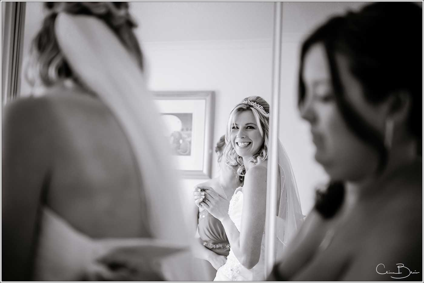 Bride smiling at her reflection while getting ready-by Hampton manor wedding photographer Clive Blair Photography