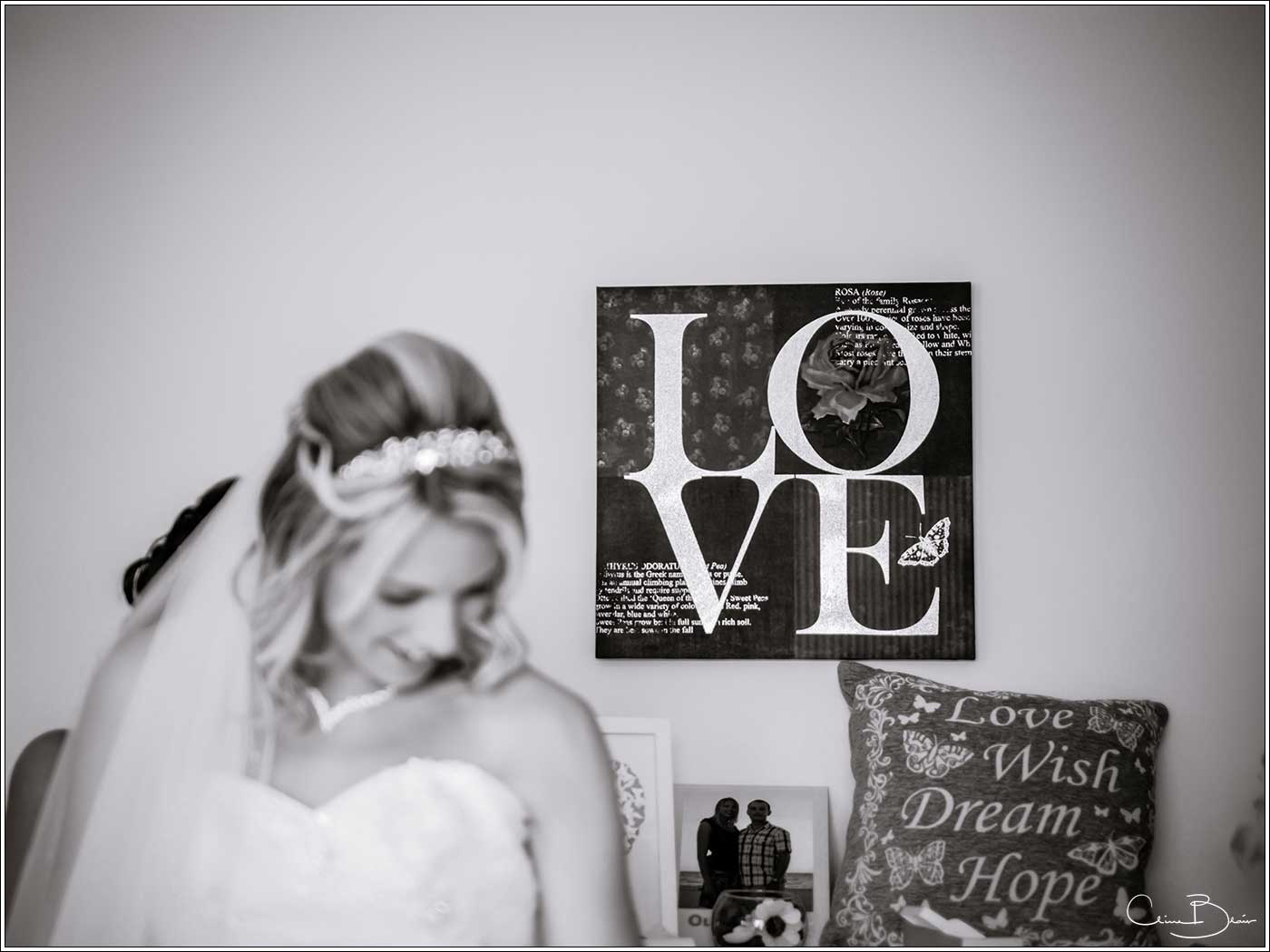 Love sign in background as bride gets ready-by Hampton manor wedding photographer Clive Blair Photography