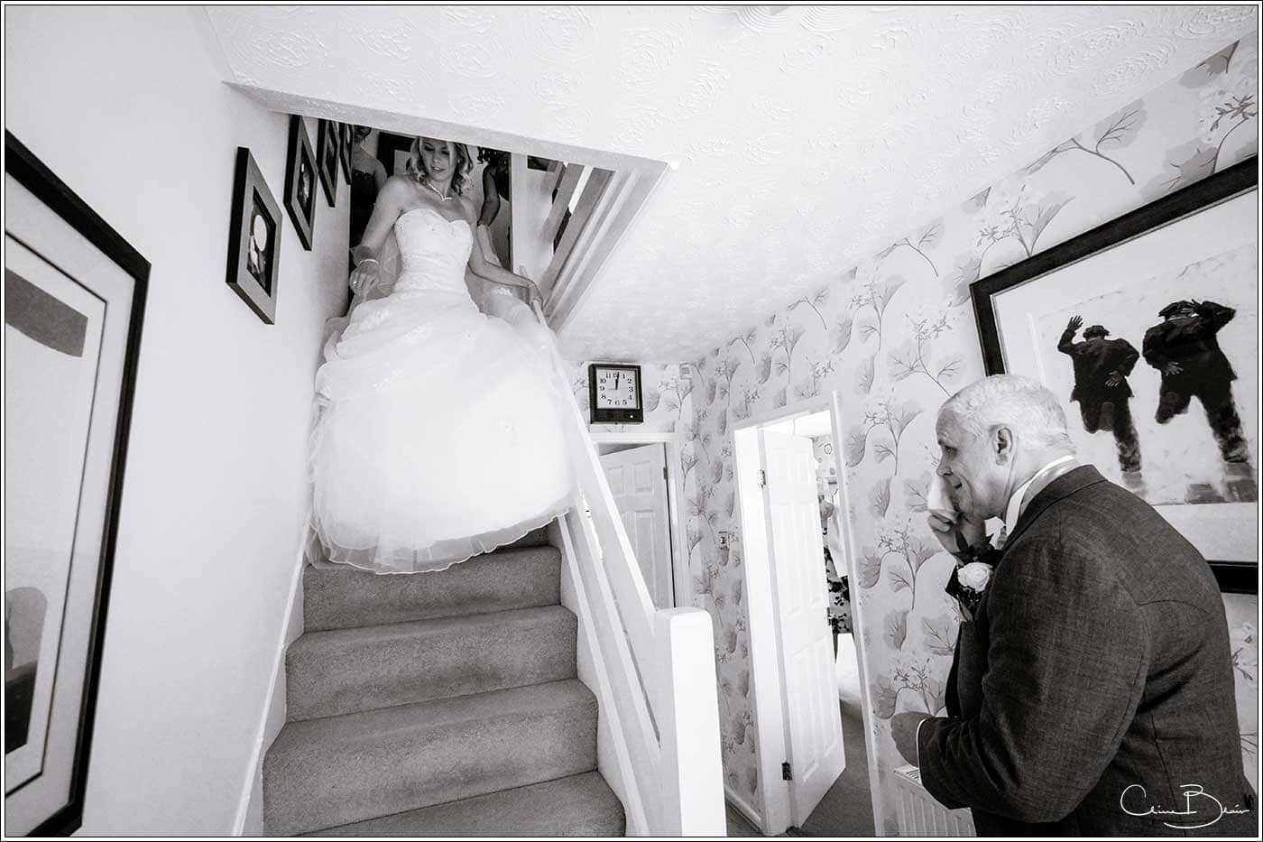Bride coming down stairs-by Hampton manor wedding photographer Clive Blair Photography