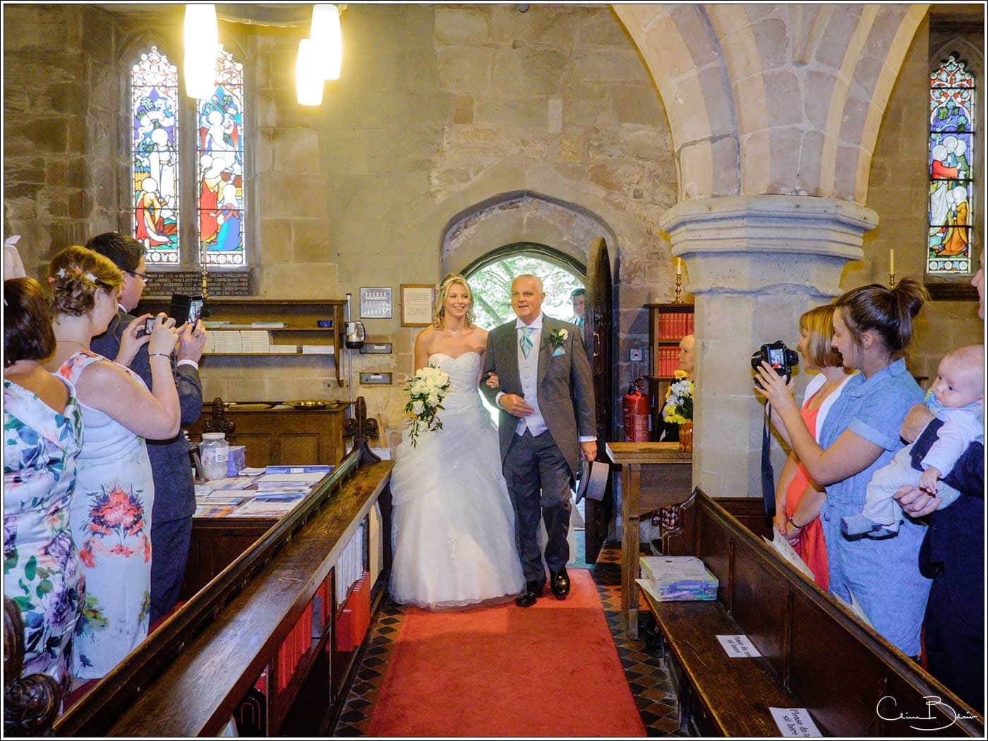 Father and bride entering the church-by Hampton manor wedding photographer Clive Blair Photography