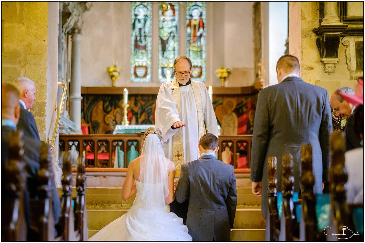 Bride and groom being blessed by minister in church-by Hampton manor wedding photographer Clive Blair Photography