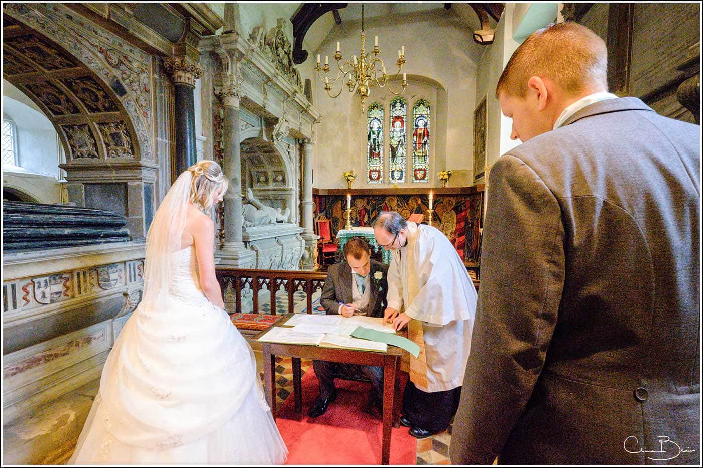 Groom signing the register-by Hampton manor wedding photographer Clive Blair Photography