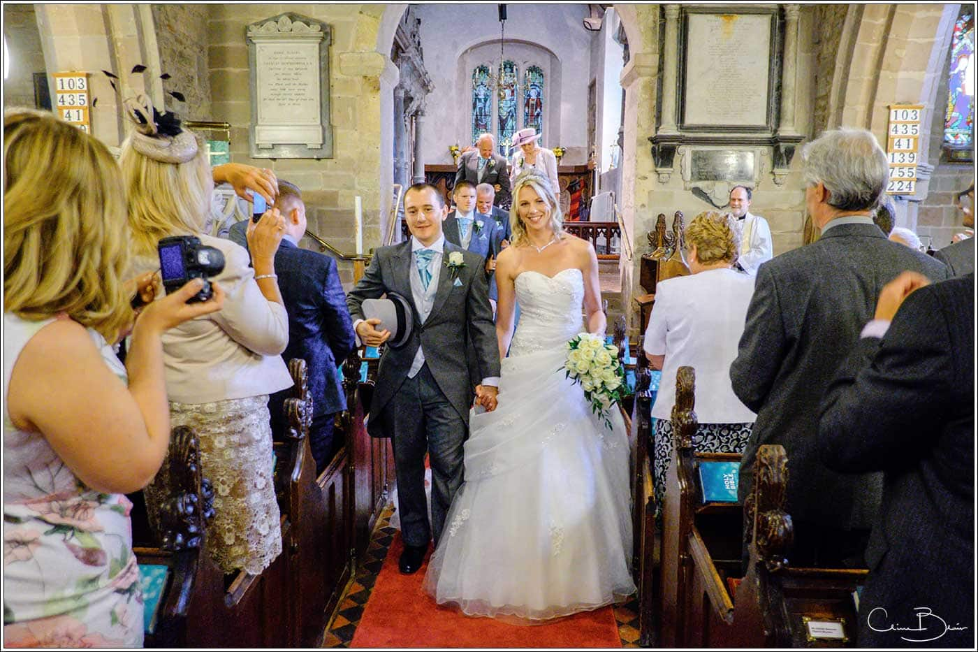 Bride and groom walking down the aisle-by Hampton manor wedding photographer Clive Blair Photography