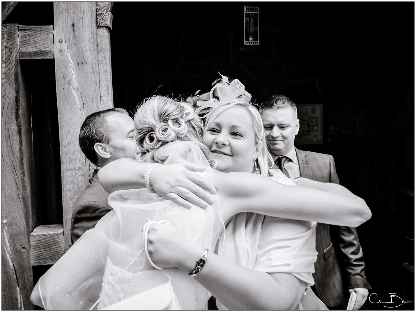 Bride being hugged after her wedding-by Hampton manor wedding photographer Clive Blair Photography