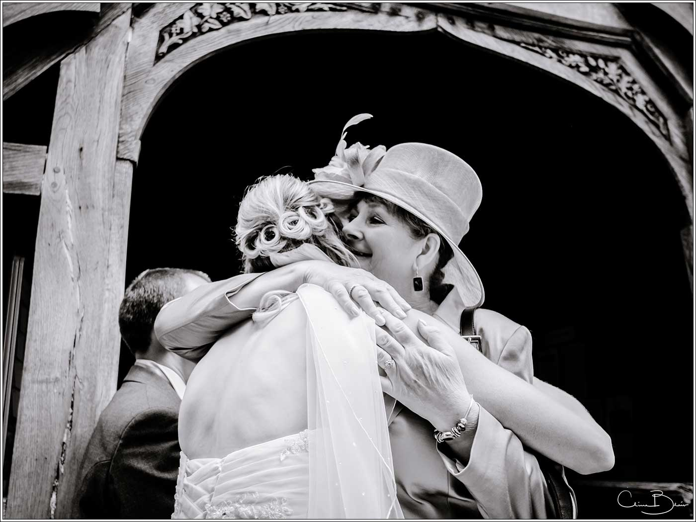 Bride being hugged by wedding guest-by Hampton manor wedding photographer Clive Blair Photography