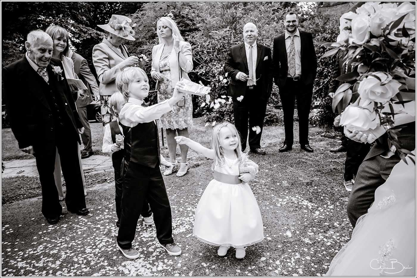 Children throwing confetti-by Hampton manor wedding photographer Clive Blair Photography