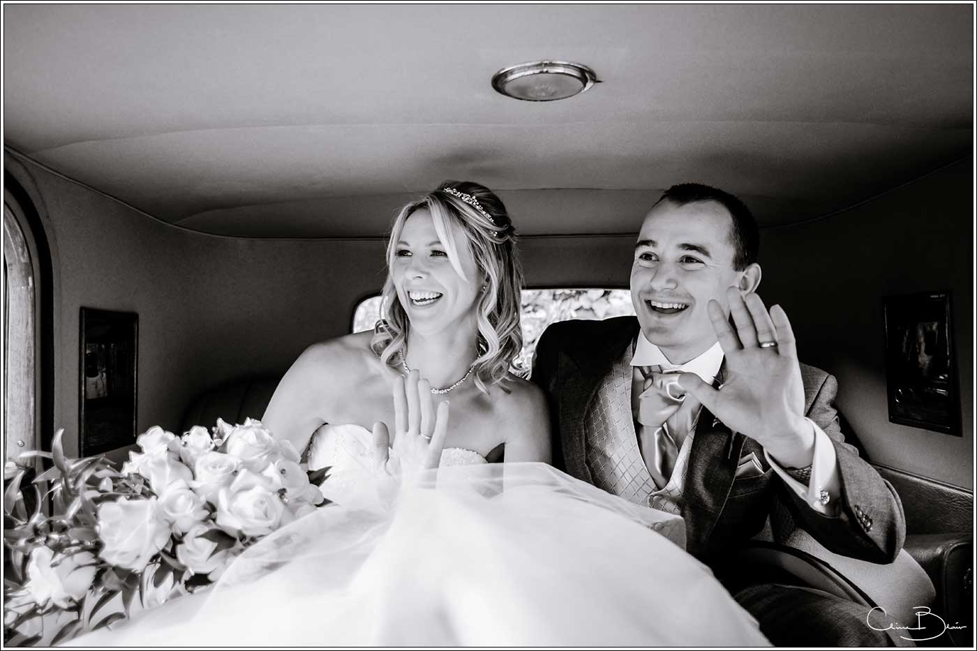 Bride and groom in wedding car-by Hampton manor wedding photographer Clive Blair Photography