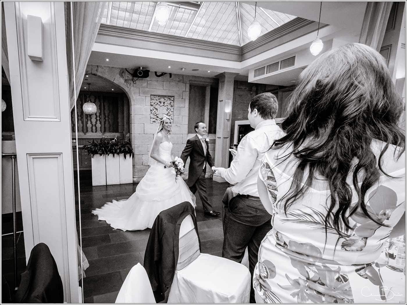 Groom leading bride into wedding breakfast room-by Hampton manor wedding photographer Clive Blair Photography