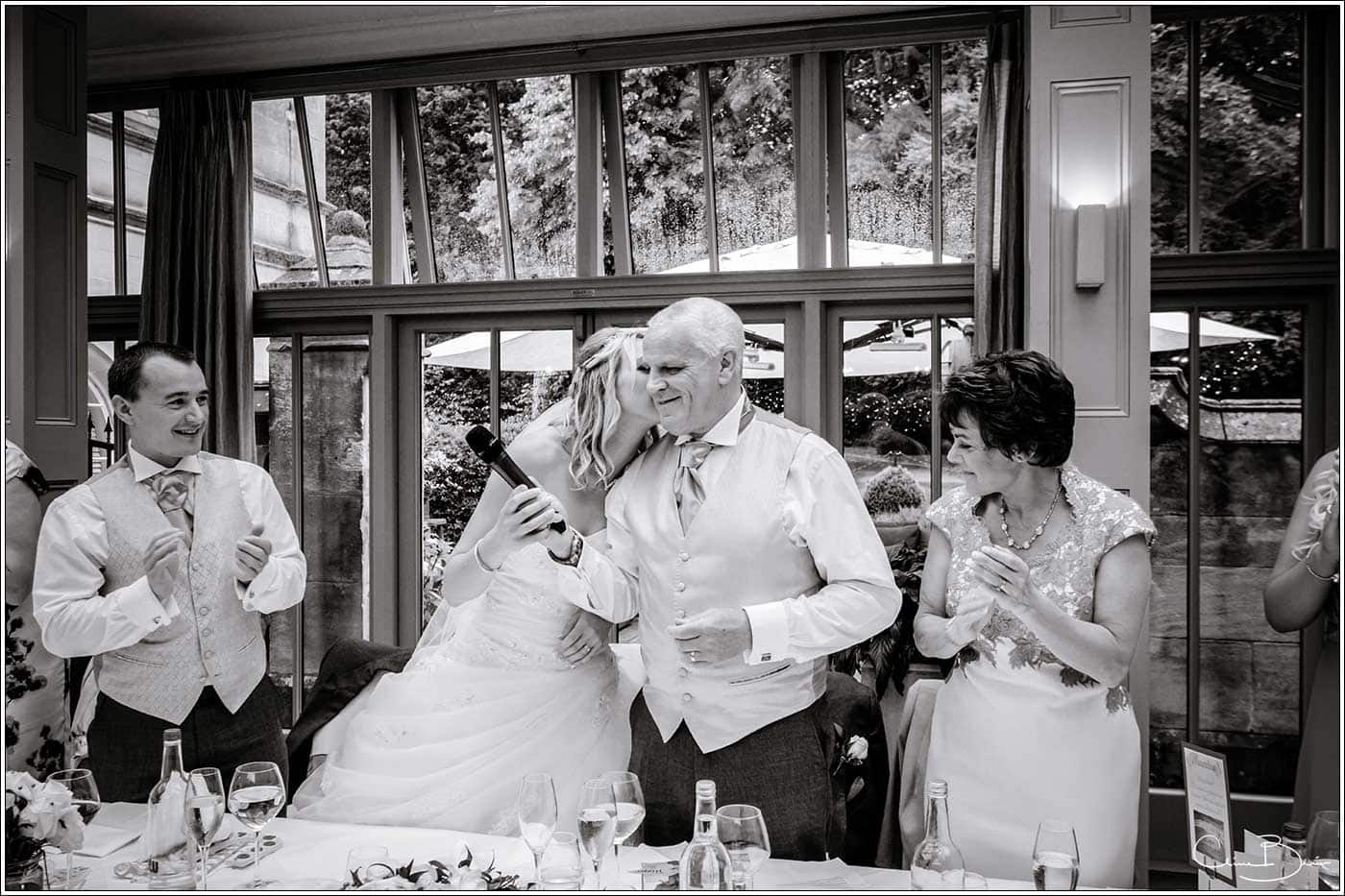 Bride giving her father a kiss after his speech-by Hampton manor wedding photographer Clive Blair Photography