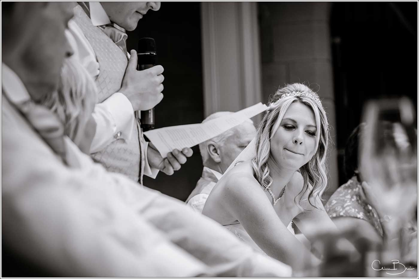 Bride holding her emotions back during the groom's speech-by Hampton manor wedding photographer Clive Blair Photography