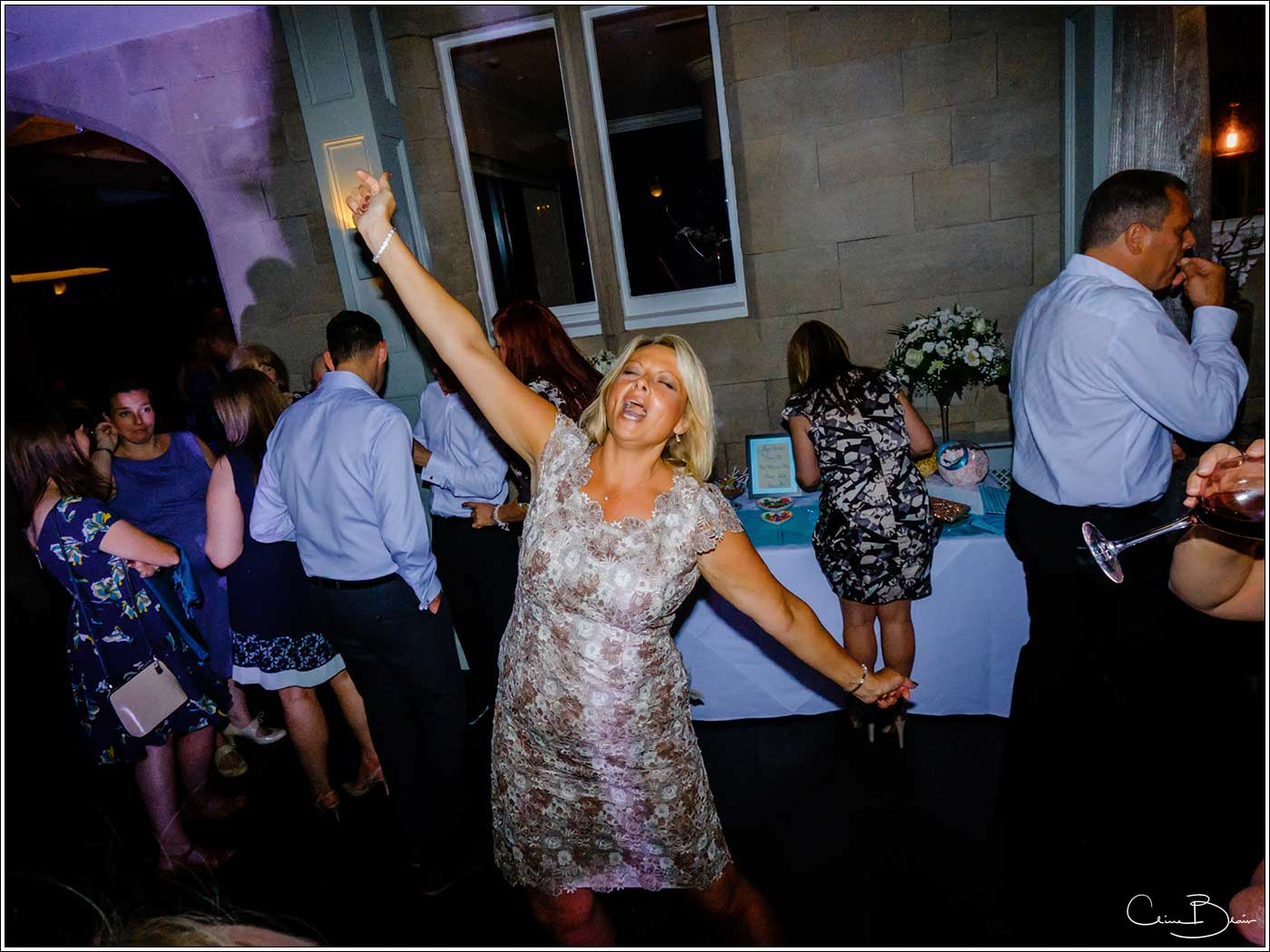 Woman singing loud during evening reception-by Hampton manor wedding photographer Clive Blair Photography