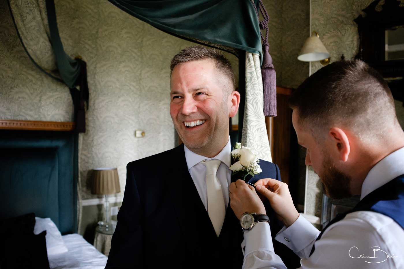 Groom having his buttonhole sorted by Grafton Manor wedding photographer Clive Blair Photography