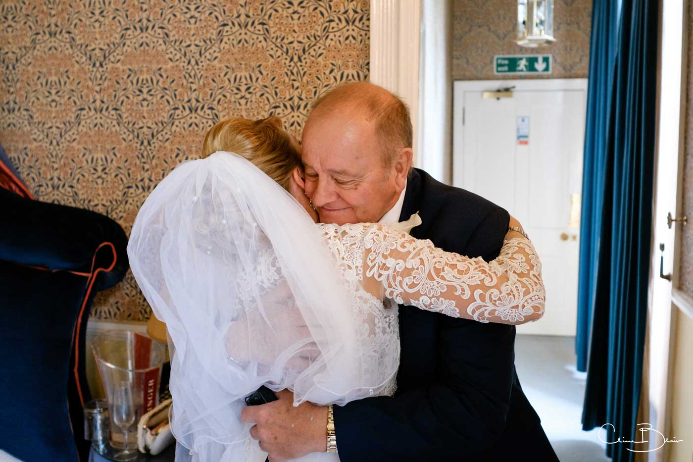 Father hugging his daughter bride as captured by Grafton Manor wedding photographer Clive Blair Photography