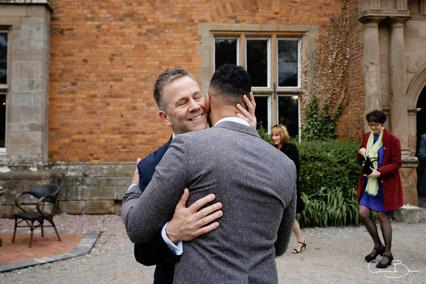 Groom hugging guest outside Grafton Manor