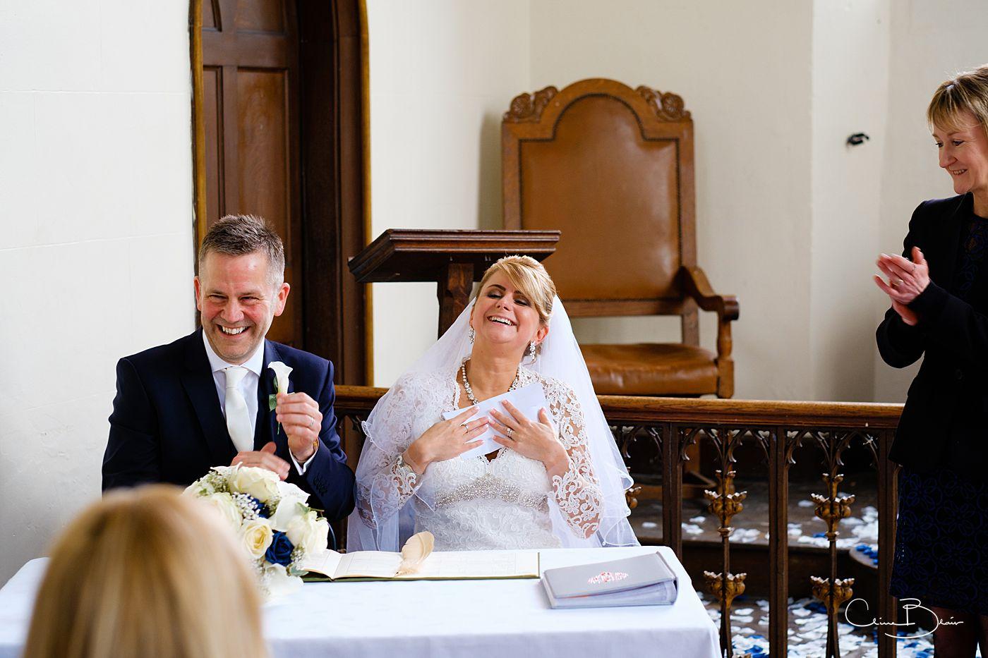 Bride hugging wedding certificate at Grafton Manor