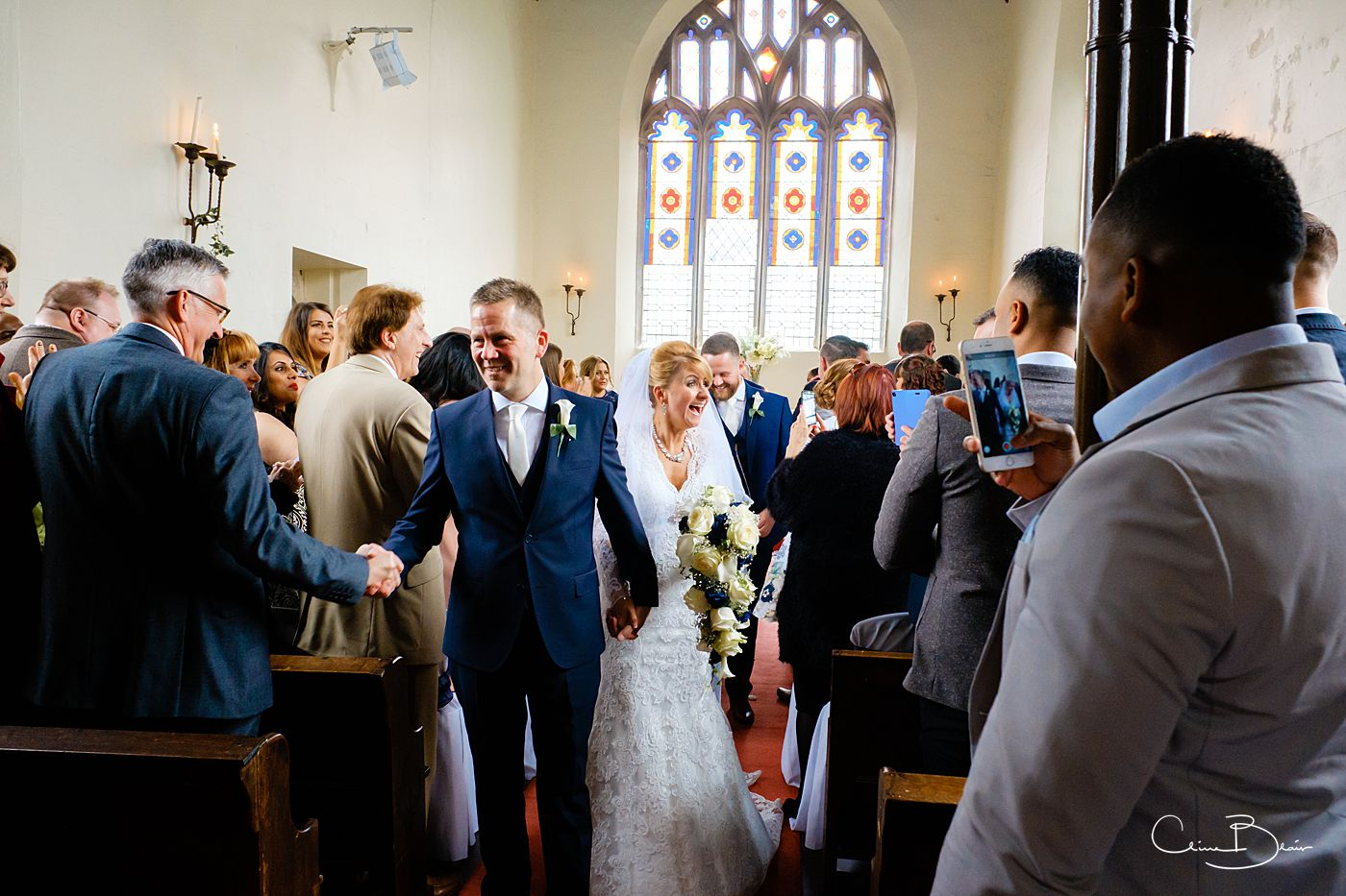 Groom and bride walking down the aisle at the chapel at Grafton Manor as captured by Grafton Manor wedding photographer Clive Blair Photography