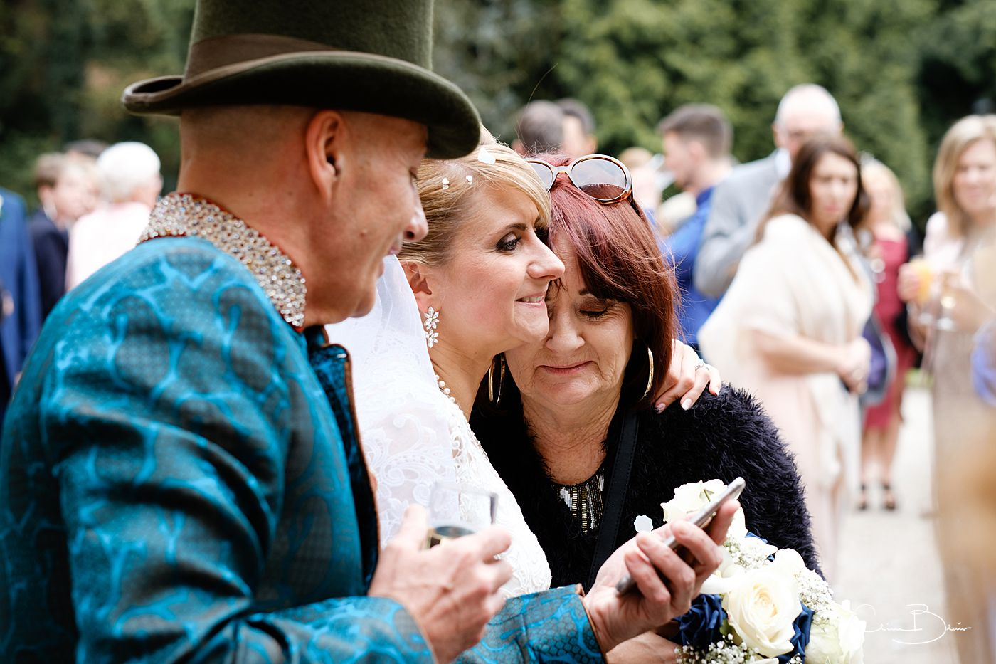 Bride being hugged by guest at Grafton Manor as captured by Grafton Manor wedding photographer Clive Blair Photography