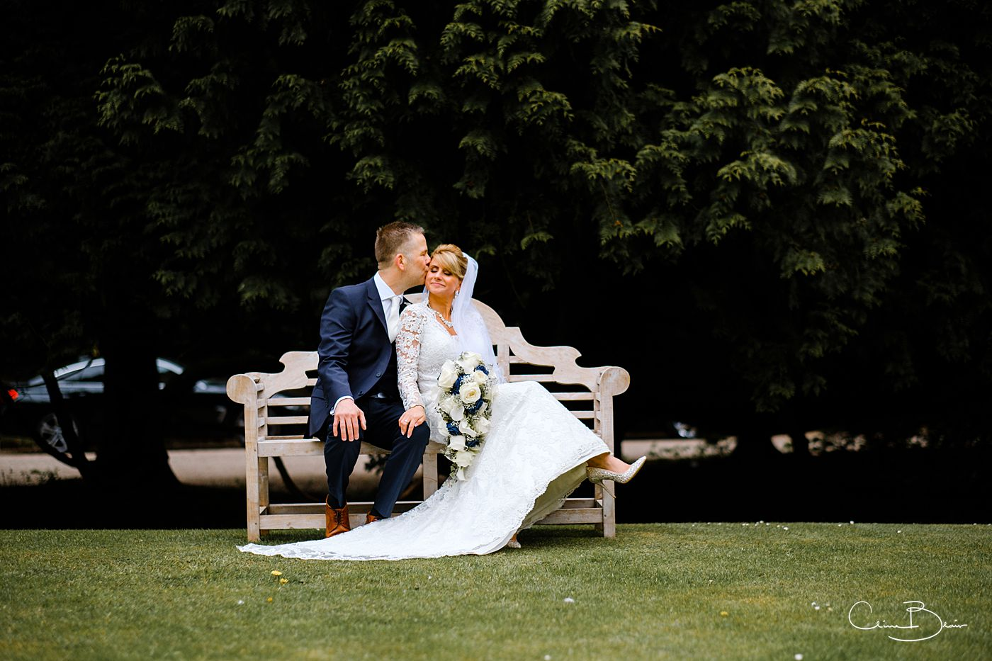 Groom tenderly kissing his bride while sitting together on a bench at Grafton Manor