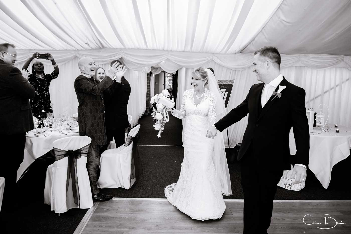 Bride and groom being cheered by guests as they enter for their wedding breakfast at Grafton Manor