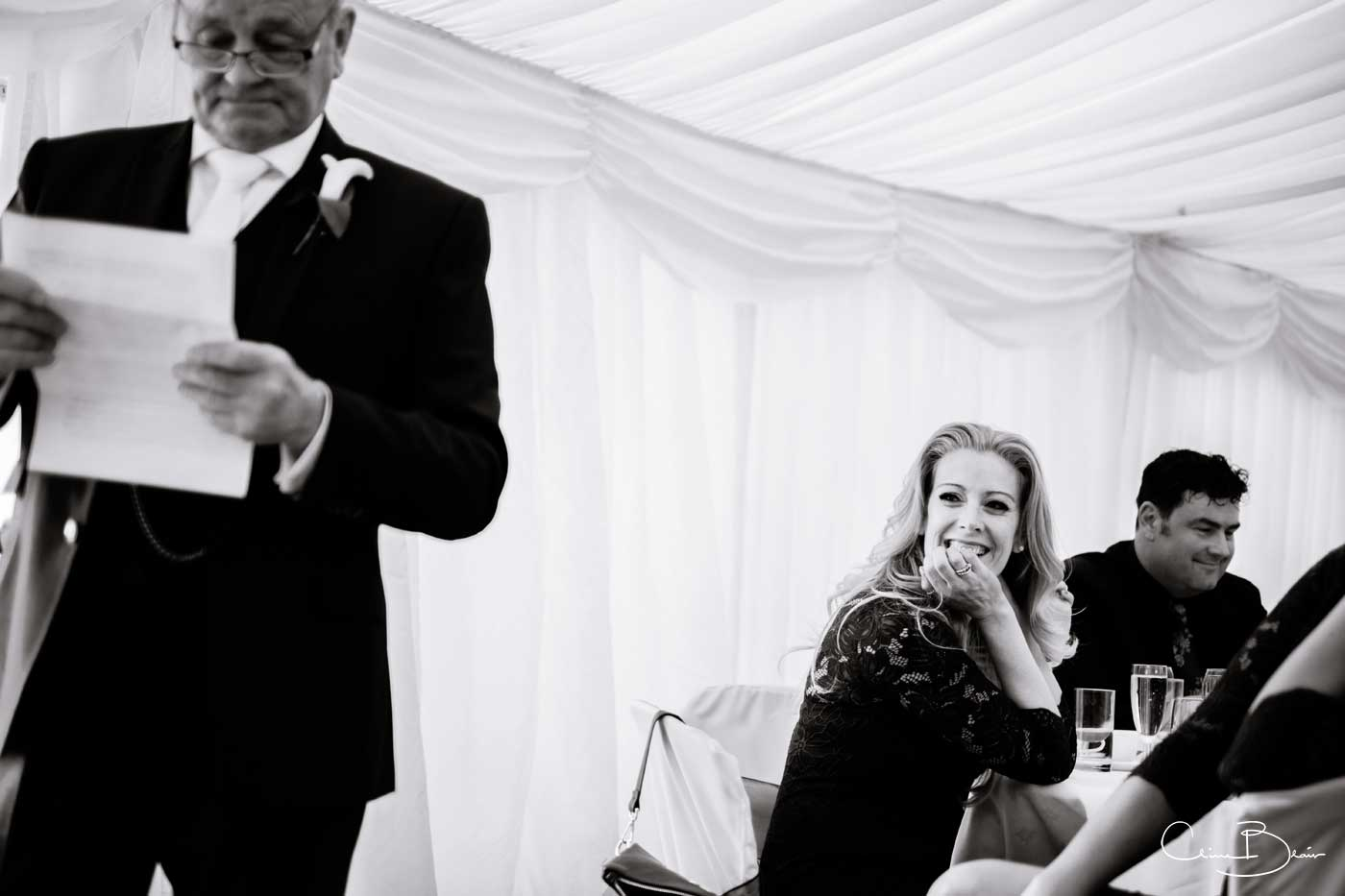 Bridesmaid laughing during the speeches in the marquee at Grafton Manor