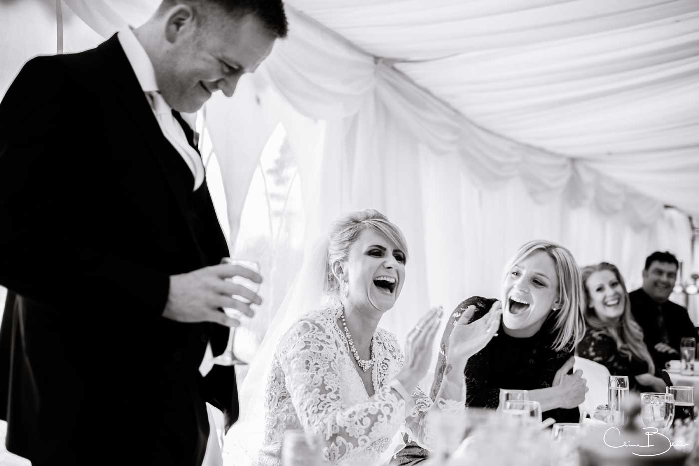 Happy bride and maid listening to speeches at Grafton Manor