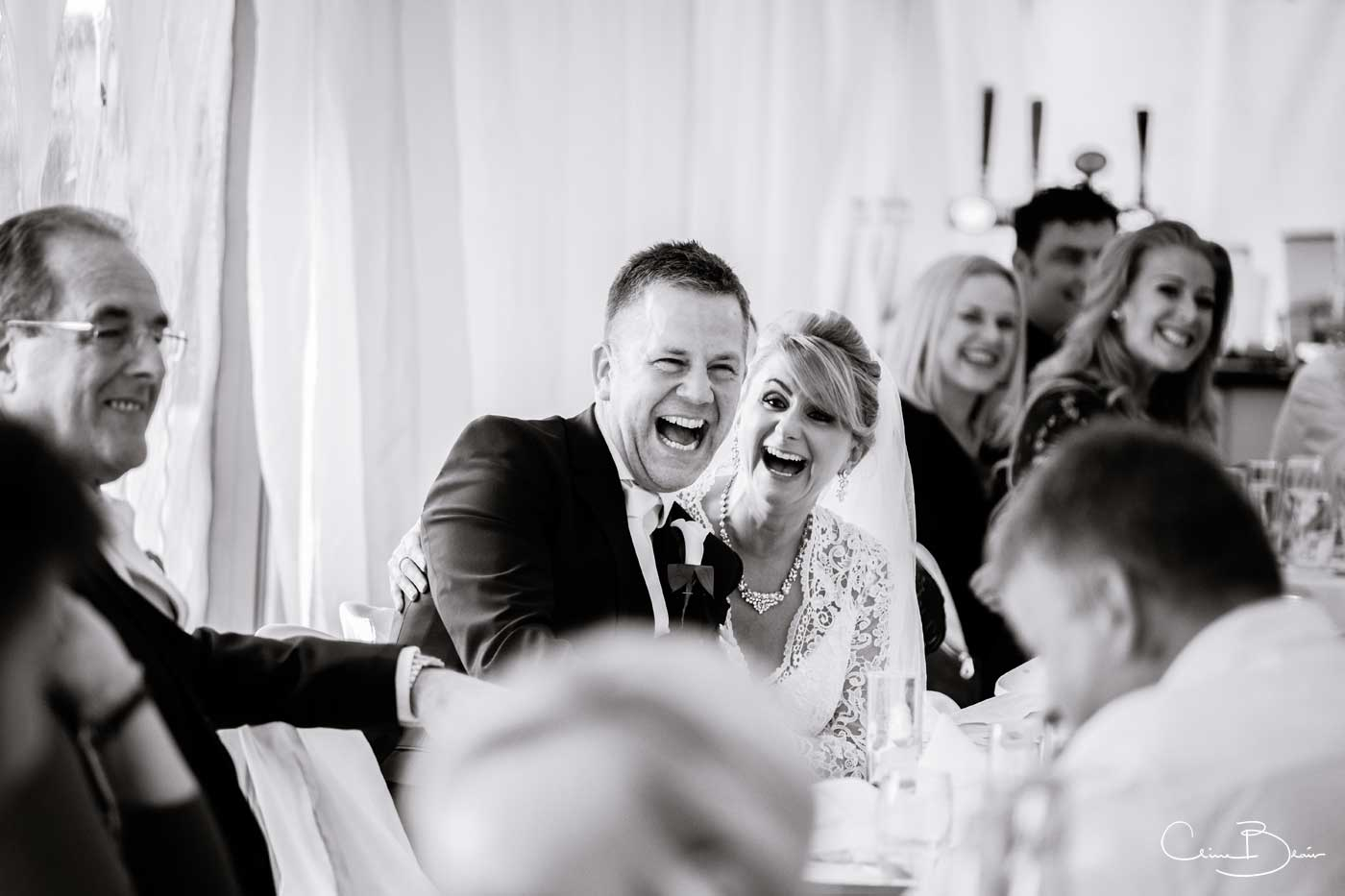 Bride and groom listeing to funny speeches at Grafton Manor