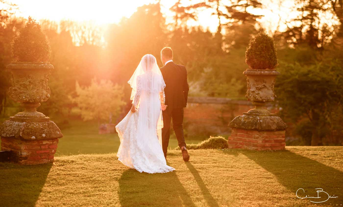 Bride and walking walking into the sunset at Grafton Manor as captured by Grafton Manor wedding photographer Clive Blair Photography