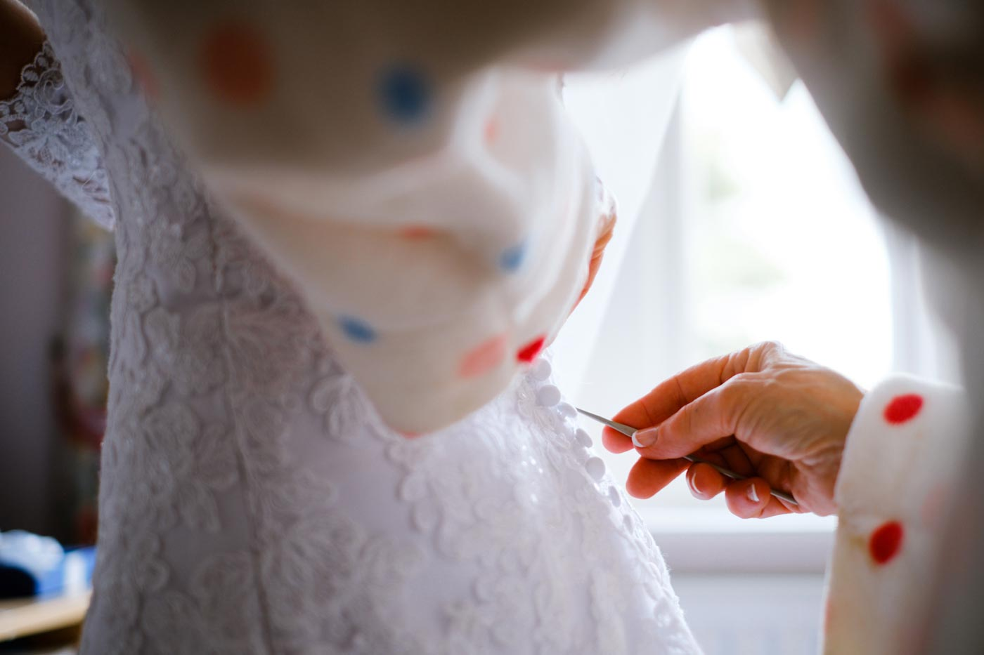 Mother of bride using crochet hook to button up the wedding dress