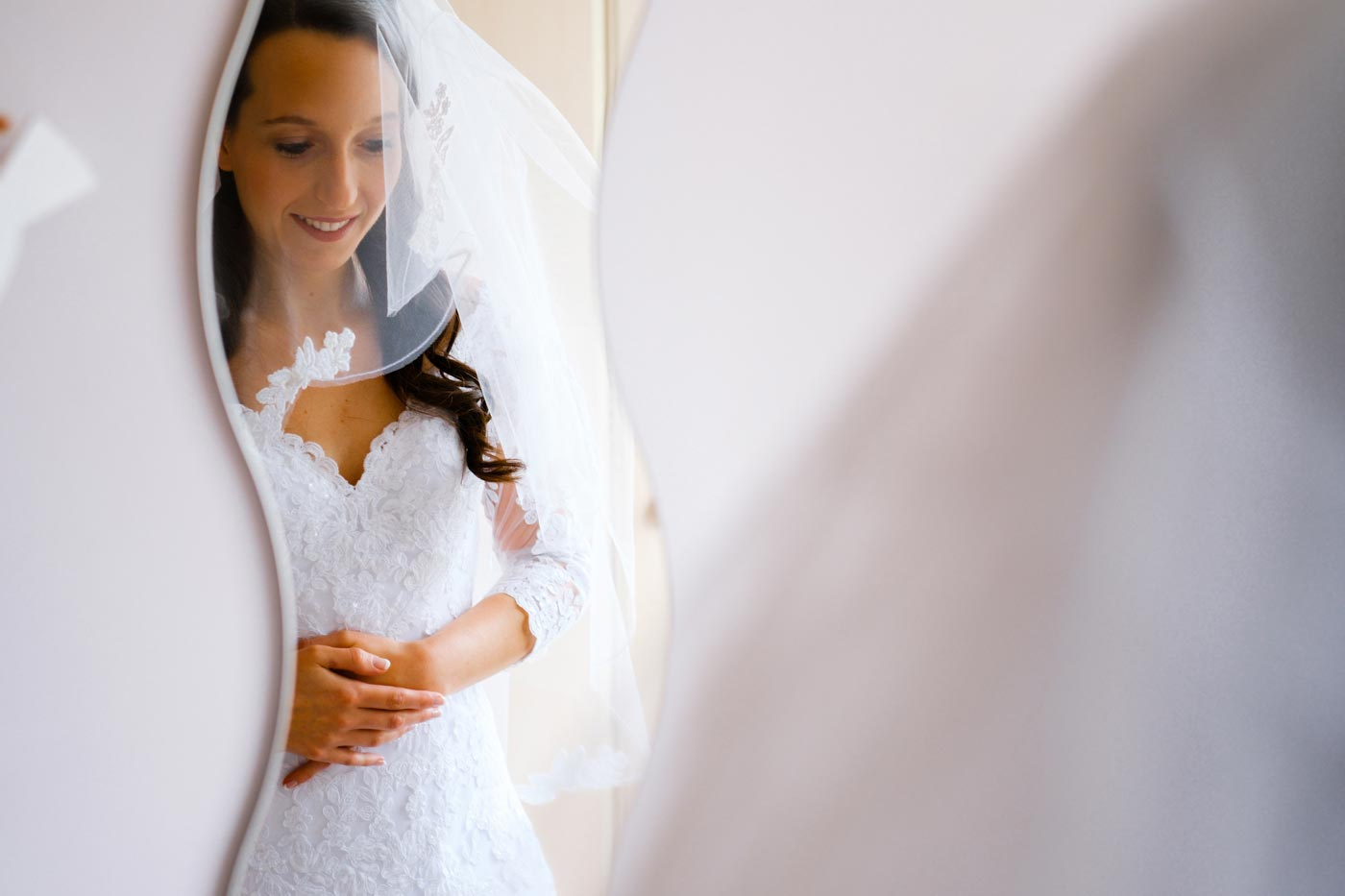 Bride in reflection in mirror as she gets ready in the morning