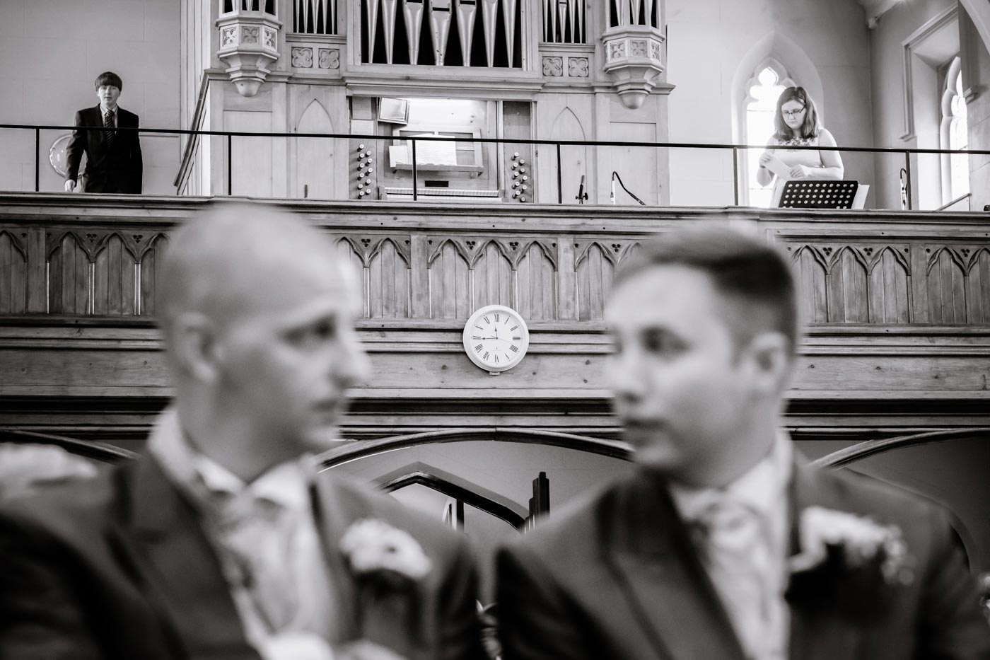 Groom and best man chatting while clock in focus in the background