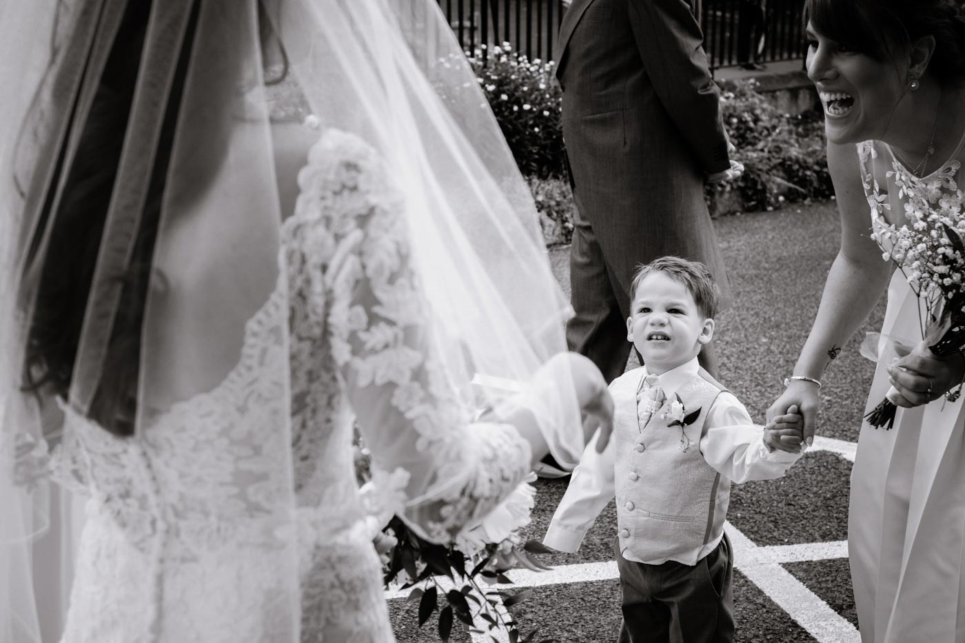 Page boy watching bride as they enter the wedding ceremony