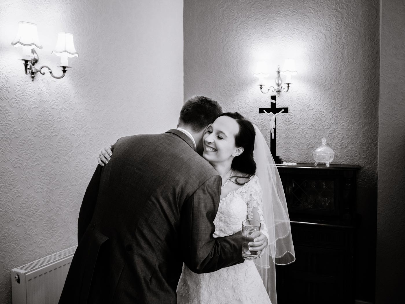 Bride being hugged after signing the register
