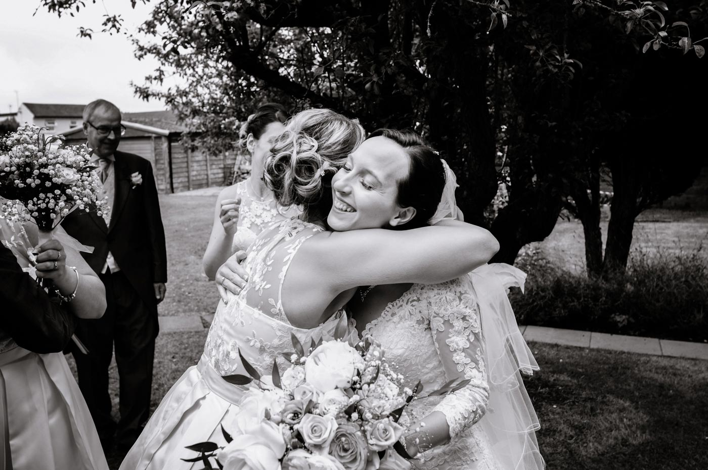 Bride being hugged after her wedding