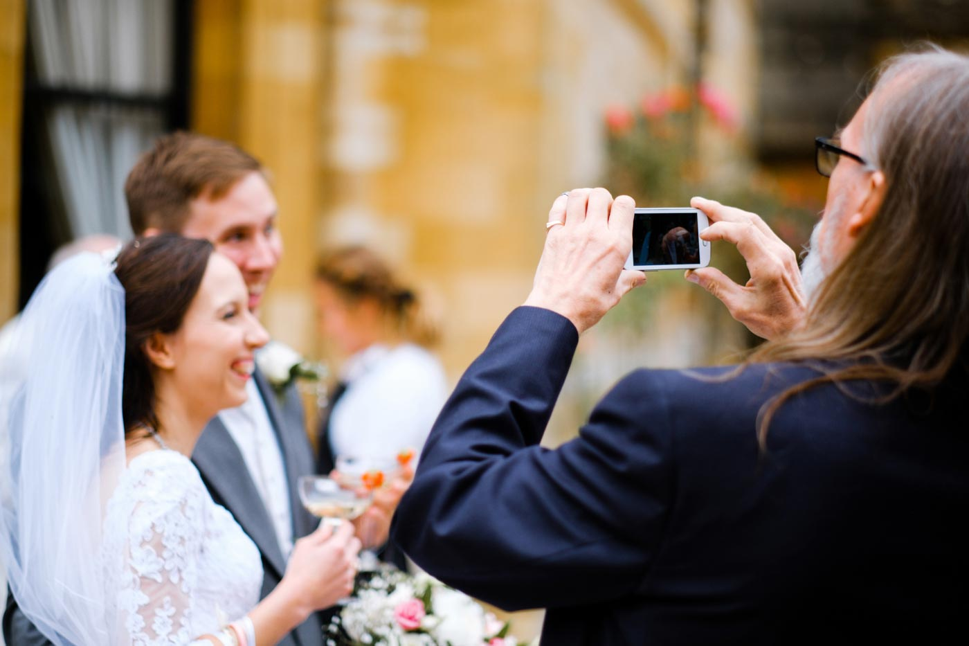 Guest taking photo on his phone of the bride and groom